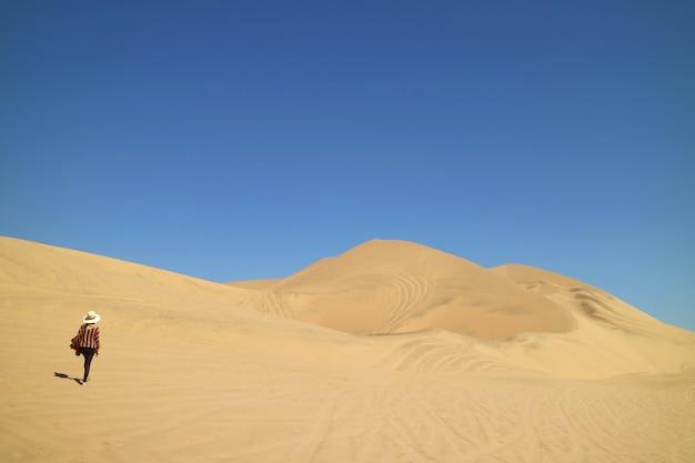 南アメリカ、ペルーのイカ地方のhuacachina砂漠の素晴らしい砂丘の上を歩く女性