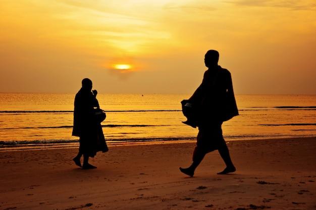 僧侶のシルエットは、ビーチ、huahin、タイで歩く