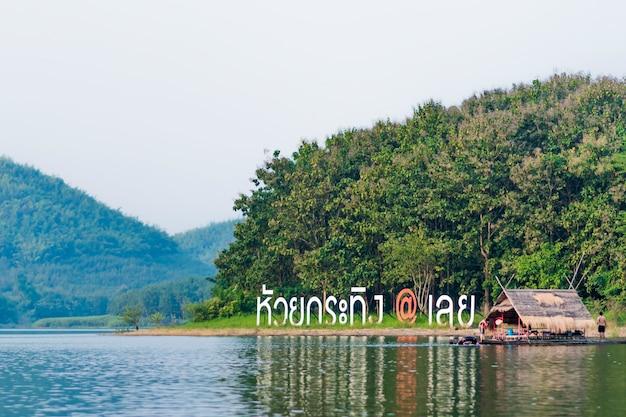 ルーイ県のフアイクラシング貯水池。銘板の近くに水と山と浮かぶいかだの景色を眺めることができます。