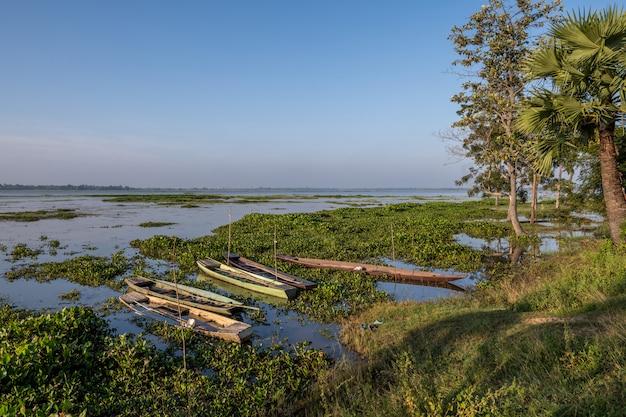 曇り空の自然な背景、スリン、タイで屋外の森の木の近くの緑の草とhuay saneng湖の水に古い浸水木製ボート