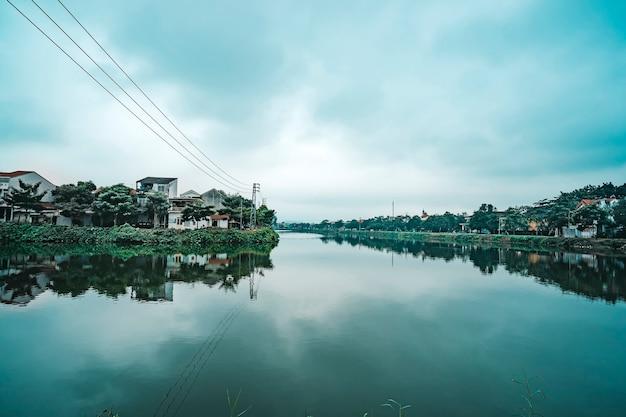 フエ、ベトナム。バックグラウンドで市内中心部の都市の池。湖の2階建ての邸宅。雲が水に反射しました。