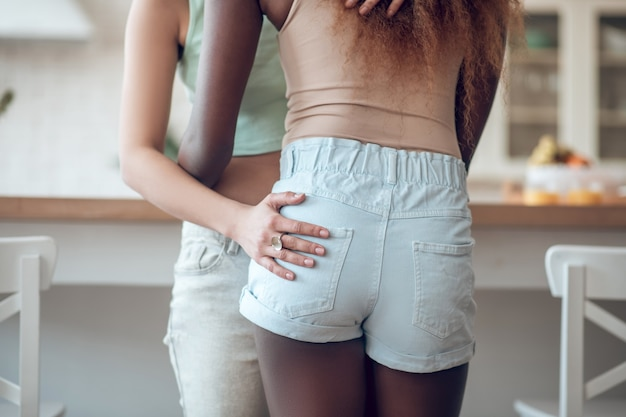 Hug, feeling. two girlfriends tenderly embracing waist and hips standing in kitchen during day, faces are not visible
