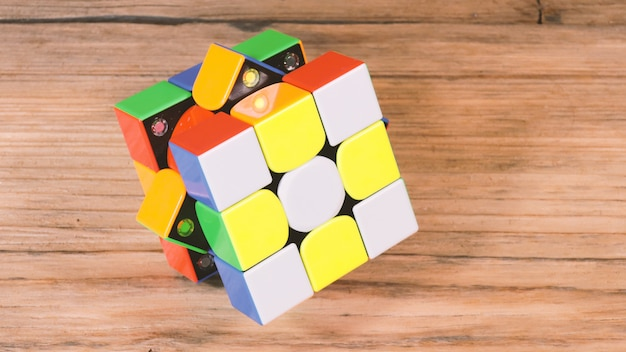 Huge 3x3 rubik's cube on the wooden table.