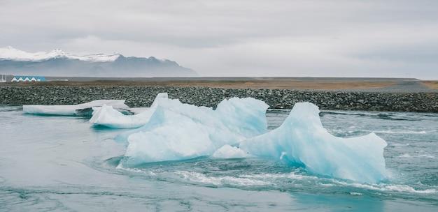 Huge blocks of ice on glacial river and blue icebergs on jokulsarlon glacier lake.