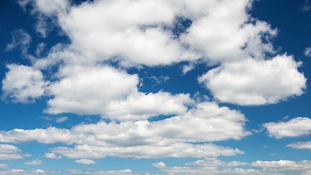 白い雲と巨大な青い空。自然の背景。アンダーレイに使用できます。