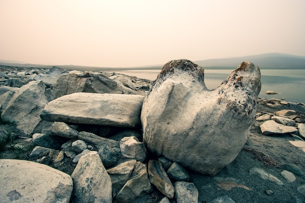 Огромные валуны у озера туманным утром