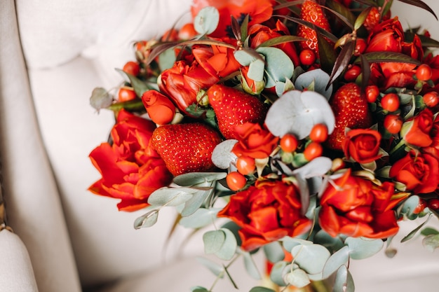 A huge bouquet of beautiful red roses with strawberries lies on the chair.