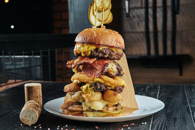Огромная бургерная башня с 5 котлетами из говядины, плавленым сыром, луком, картофелем, огурцами, соусом. крупным планом, вертикальный