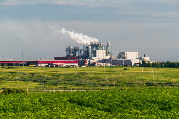 A huge concrete plant with pipes among the fields