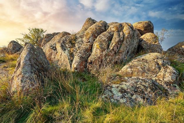 그림 같은 우크라이나와 그 아름다운 자연의 따뜻한 태양으로 가득한 초원에 식물로 덮인 오래된 석재 광물의 거대한 매장지