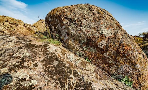 Огромные залежи старых каменных минералов, покрытых растительностью, на лугу, залитом теплым солнцем в украине и ее красивой природе.