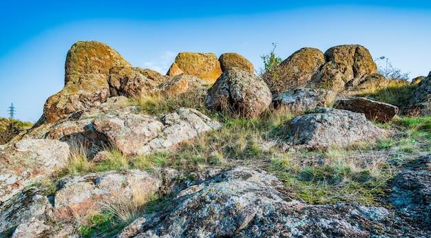 우크라이나의 따뜻한 태양과 아름다운 자연으로 가득한 초원에 식물로 덮인 오래된 석재 광물의 거대한 매장지