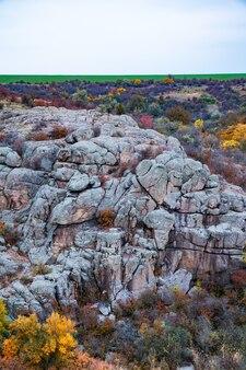 Огромные залежи старых каменных минералов, покрытые растительностью на лугу, залитом теплым солнцем.