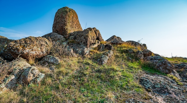 Huge deposits of old stone minerals covered with vegetation in a meadow filled with warm sun in ukraine and its beautiful nature
