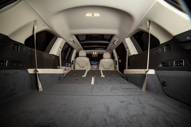 Suv의 프리미엄 밝은 색상 내부에 있는 거대한 빈 자동차 트렁크. 평평한 바닥으로 접힌 프리미엄 자동차의 뒷좌석. 배면도