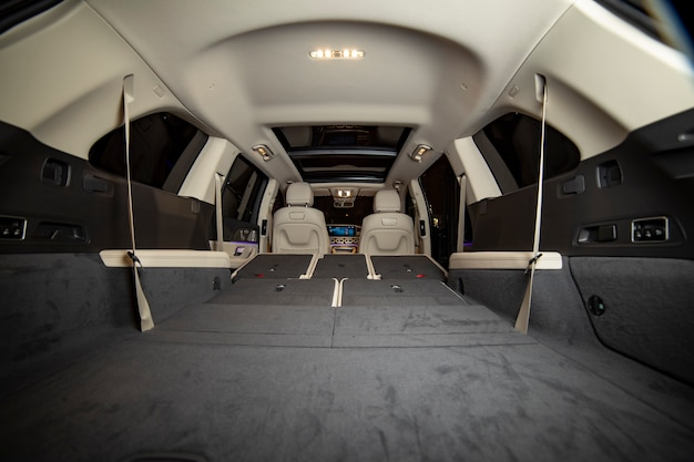 Huge empty car trunk in premium light color interior of suv. rear seats in premium car folded in flat flor. rear view
