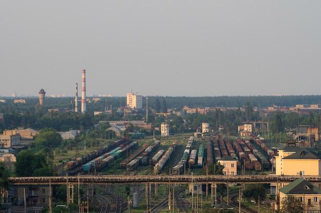 Огромная грузовая станция с множеством поездов и вагонов для перевозки грузов.
