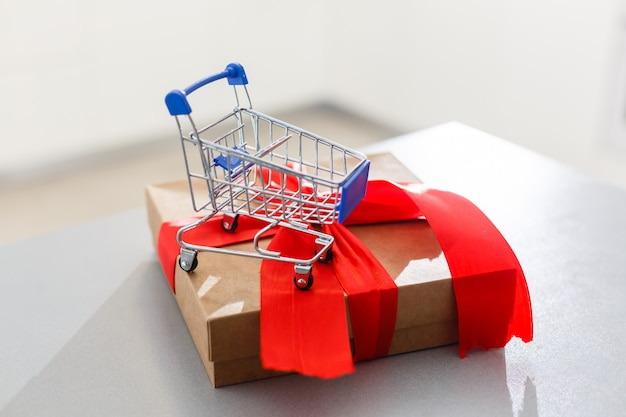 A huge gift with a red ribbon and a shopping cart