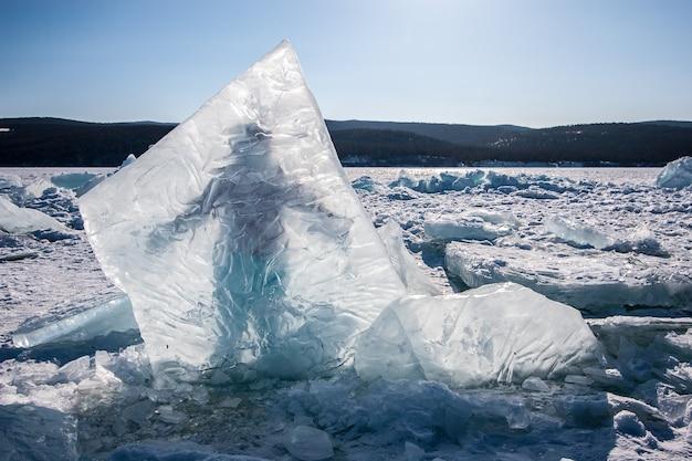 バイカル湖に凍った巨大な氷片、その後ろに男が立っている