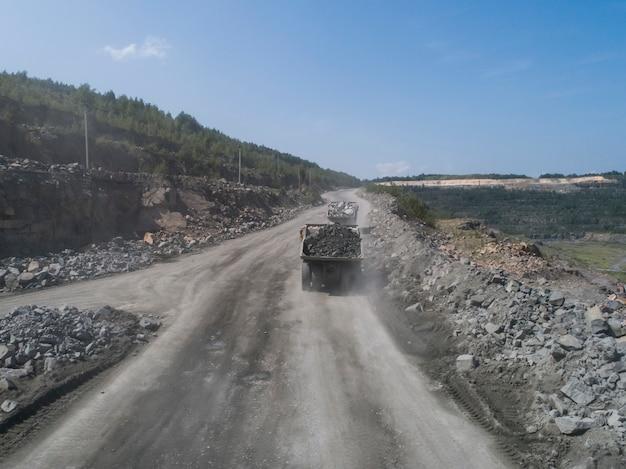 石の採石場の道路にある巨大な産業用ダンプトラックは、ドローンから撮影した大理石または花崗岩を輸送します
