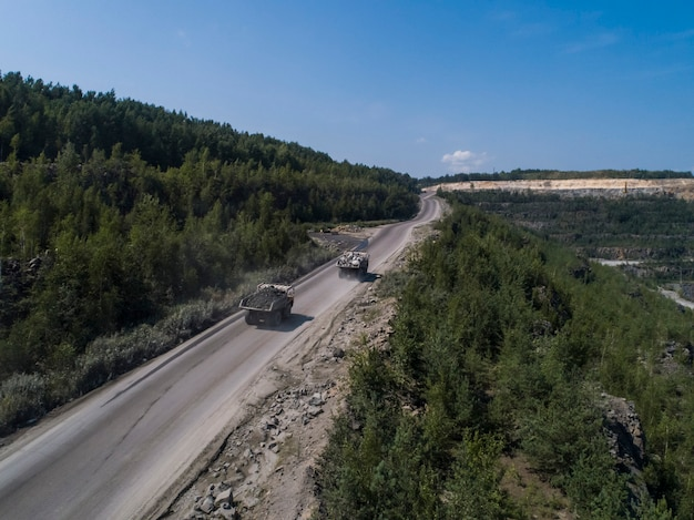Huge industrial dump truck in a stone quarry loaded transporting marble or granite shot from a drone