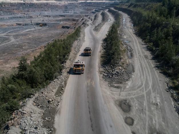石の採石場の巨大な産業用ダンプは、花崗岩ショットドローントップショットをロード