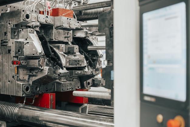 加熱された材料を金型に射出することにより、プラスチック製品の準備ができた固定具のない巨大な射出成形機