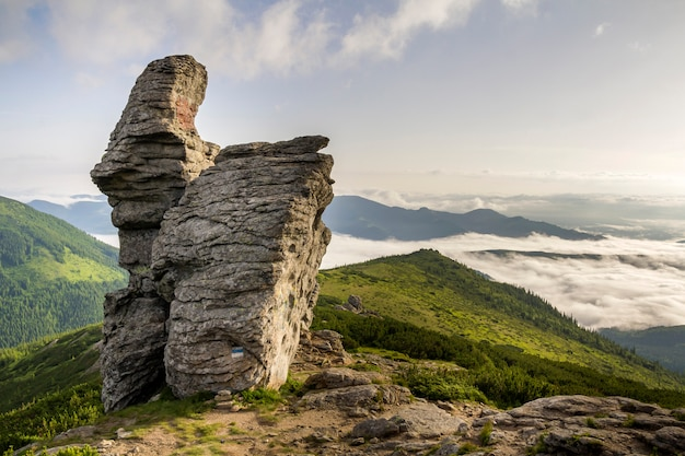 Huge limestone rocky boulder on green mountain top  of valley filled with white puffy clouds and fog, view of covered with evergreen forest mountain ridge and clear blue copy space sky.