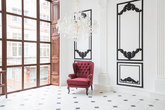 독특한 인테리어의 거대한 럭셔리 화이트 홀. 바닥에 흑백 타일, 벽에 흰색과 검은 색 치장 벽토, 거울 모자이크가있는 높은 벽난로, 3m 크리스탈 샹들리에