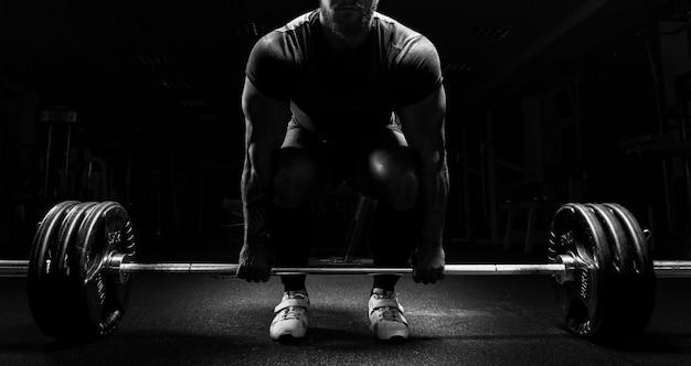 Гигантский мужчина готовится выполнить упражнение под названием становая тяга. смешанная техника