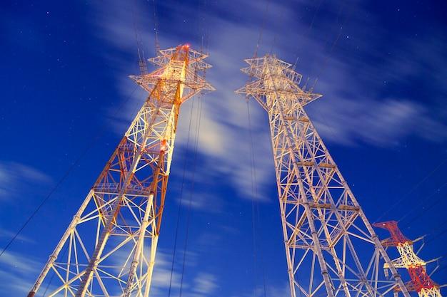 Huge metallic pylons against night windy sky