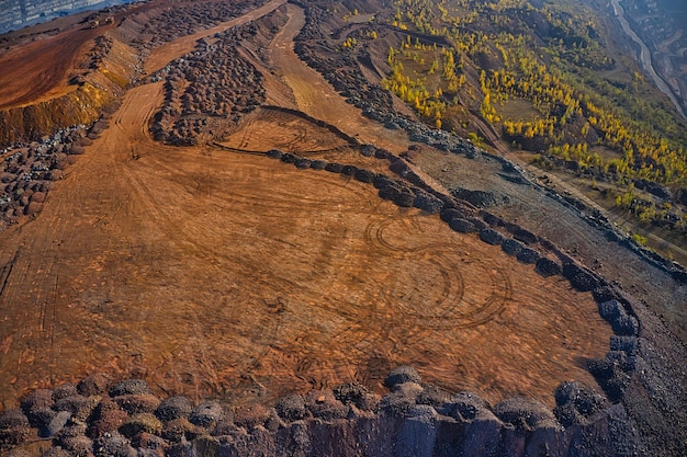 Huge mounds of waste iron ore near the quarry. belaz trucks driving in mining factory, mine quarry in ukraine