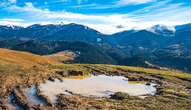 A huge muddy puddle with disgusting mud on a small path in the carpathian mountains against beautiful autumn hills