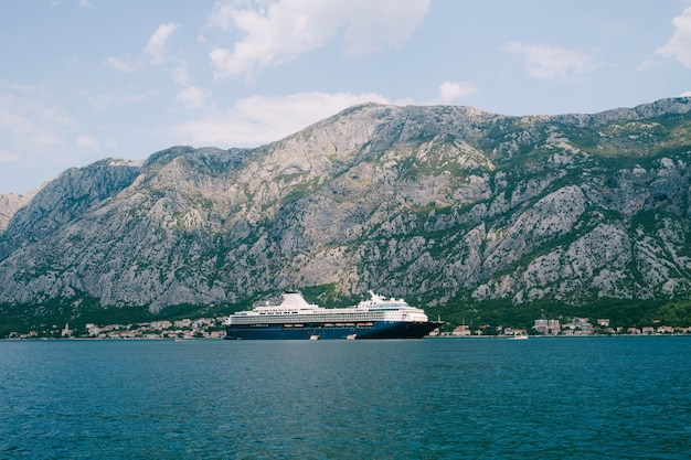 A huge multideck cruise liner in kotor bay against the backdrop of a mountain above the city of