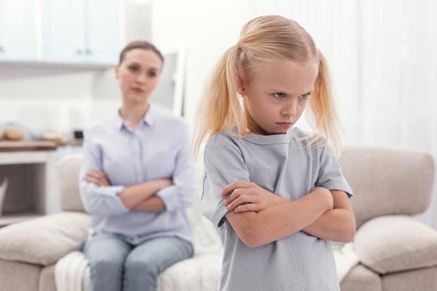 Огромное нарушение. неудовлетворенная злая недовольная девушка скрещивает руки, хмурясь и поворачиваясь спиной к маме