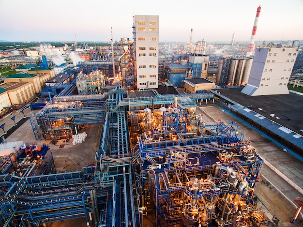 Huge oil refinery with metal structures, pipes and distillation of the complex with burning lights at dusk. aerial view