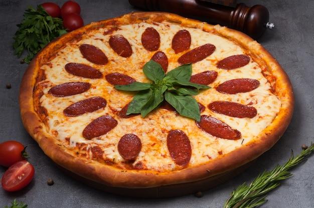 バジルで飾られたモッツァレラチーズの巨大なペパロニピザ