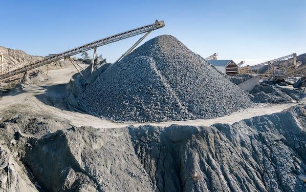 Огромная куча гравия и оборудования на камнедробильно-сортировочном заводе, над голубым небом