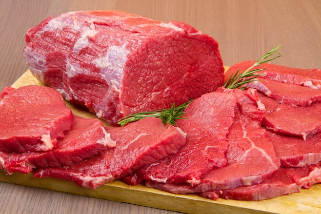 Huge red meat chunk and steak on wood table