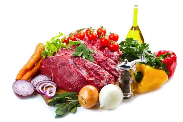 흰색 배경 위에 절연 야채와 함께 거대한 붉은 고기 덩어리