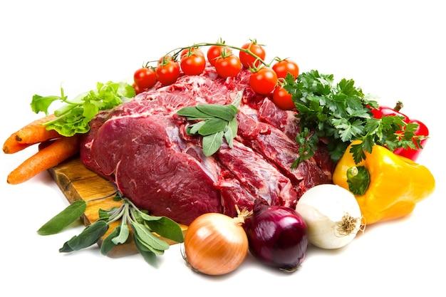흰색 테이블 위에 절연 야채와 함께 거대한 붉은 고기 덩어리