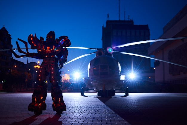 Huge robot-transformer standing in front of military helicopter silhouette.