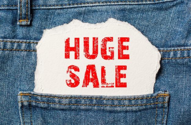 Огромная распродажа на белой бумаге в кармане синих джинсовых джинсов