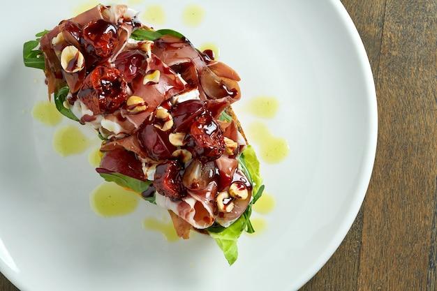 생햄, 브리 치즈, 혼합 샐러드, 포도, 햇볕에 말린 토마토와 호밀 빵에 견과류가 들어간 거대한 샌드위치는 나무 테이블에 흰색 접시에 제공됩니다.