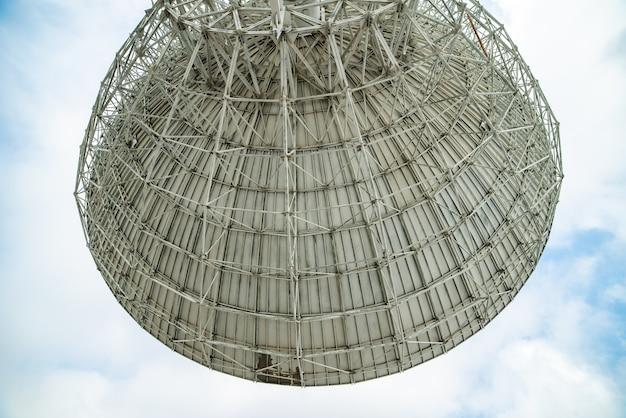 Огромная спутниковая антенна для связи и приема сигнала с планеты земля. обсерватория ищет радиосигнал в космосе на закате.