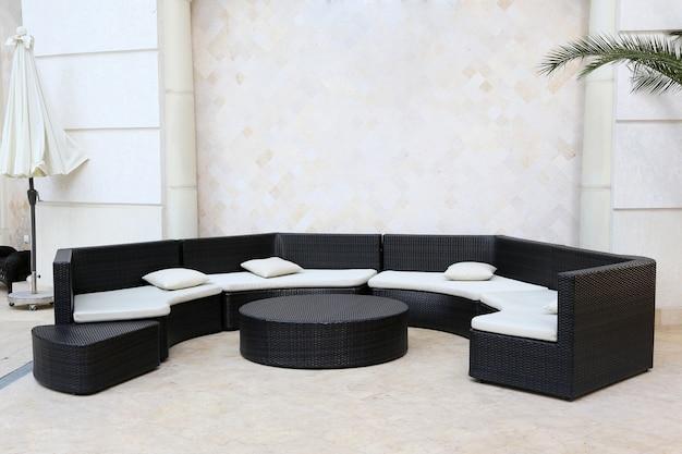 Огромный полукруглый черный диван с белыми подушками и столиком в интерьере гостиницы