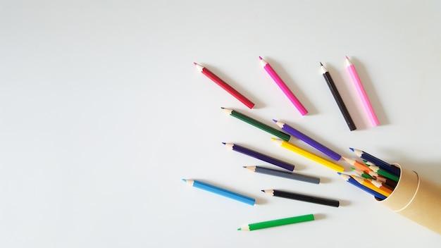 白いテーブルの背景にカラフルな鉛筆の巨大なセット。上面図。