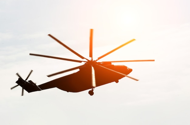 Huge silhouette of a helicopter flies up in the sky glare from the sun.