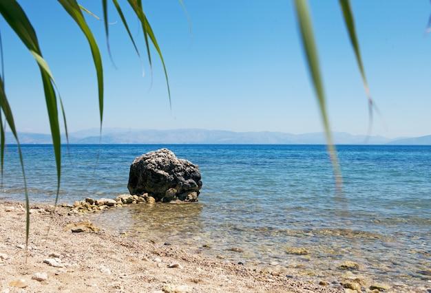 바다 해안의 거대한 돌 바위, 바닷물의 거대한 돌, 야자수 잎. 그리스 여름