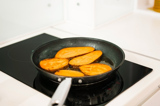 Huge sweet potatoes slices fries inside a frying pan. food preparation. roots. vegetarian. kitchen. black induction hob. meal. dish. yummy. healthy food. cooking